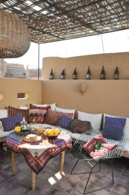 sandy walls, colorful textiles with bright patterns, Moroccan lamps and a wicker lampshade