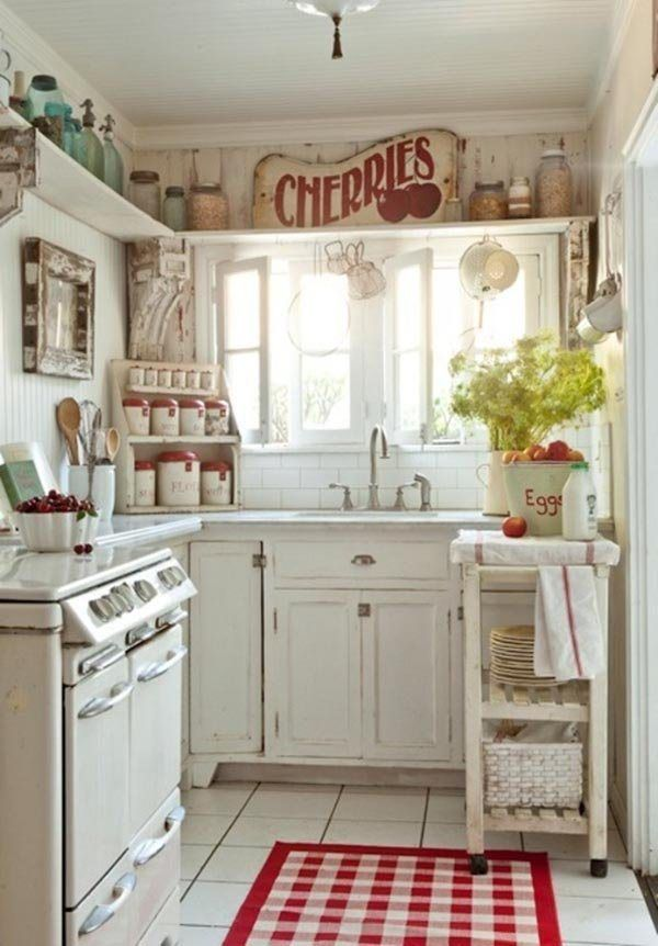 a white shabby chic kitchen with vintage cabinets and shelves, a printed rug, bright signs and greenery plus red touches
