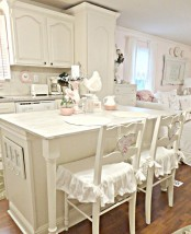 vintage and shabby chic kitchen done in neutrals, with neutral cabinets, floral prints and cute ruffle chair covers