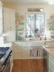 a romantic vintage and shabby chic kitchen with white cabinets, a floral cover under the sink, an aqua kitchen island and other aqua touches