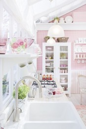 a romantic pink and white vintage kitchen with plaid wallpaper, striped paneling, white furniture and a glazed wall plus printed textiles