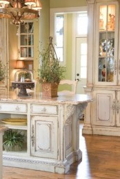 a refined shabby chic kitchen with neutral furniture, glass cabinets and a kitchen island, potted greenery and a vintage chandelier