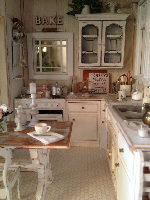 a rustic shabby chic kitchen in neutrals, with wooden walls and vintage cabinets, a shabby chic table and kitchen island and shabby chairs