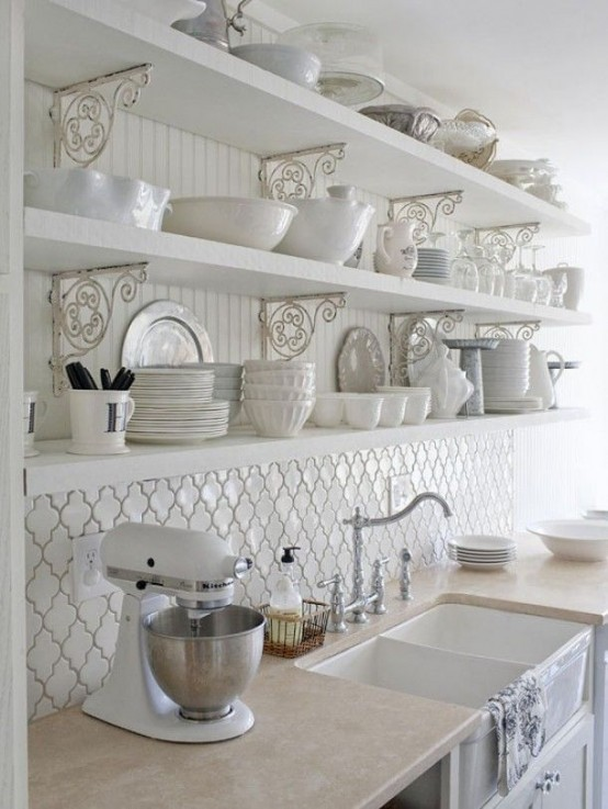 a beautiful white vintage kitchen with a chic tile backsplash, open shelving and beadboard and refined metal decorations