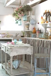 a rustic shabby chic kitchen with white walls, vintage furniture with burlap instead of doors, a shabby chic kitchen island and blooms hanging in jars over the island