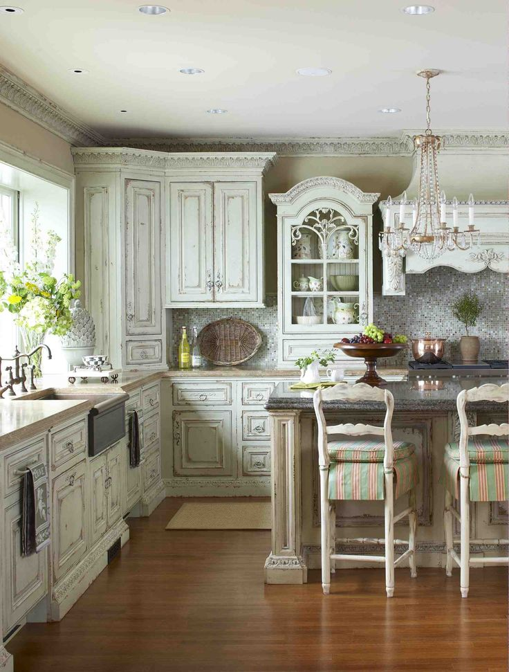 a refined shabby chic kitchen with neutral shabby cabinets, a crystal chandelier, a tan kitchen island with a black countertop