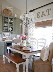 a vintage kitchen in olive green, white dining set with stained surfaces, a vintage chandelier and a leather chair