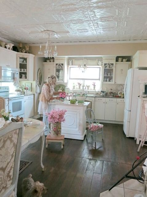a neutral shabby chic kitchen with white cabinets, a crystal chandelier, a mini vintage kitchen island and touches of powder blue and pink
