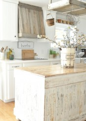 a shabby chic farmhouse kitchen in neutrals, with a shabby kitchen island, white cabinets and a weathered wood hood