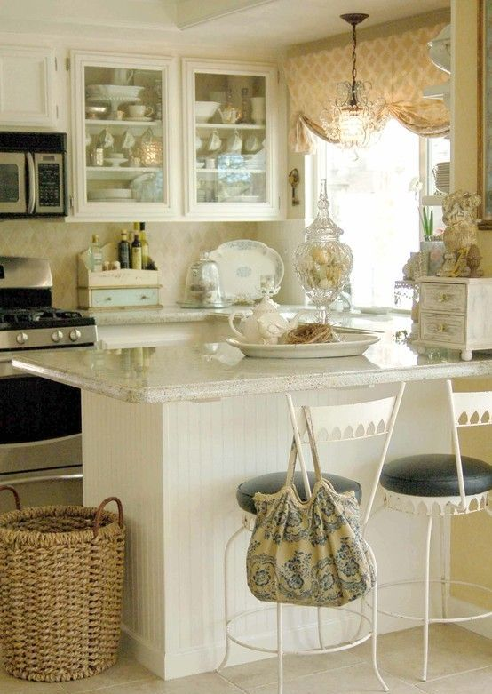 a neutral shabby chic kitchen with white cabinets, neutral tiles, a white kitchen island and a printed curtain plus white metal chairs with leather seats