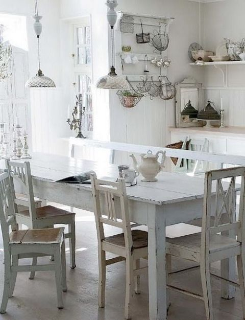 a neutral shabby chic kitchen with white cabinets, beadboard paneling, a shabby chic dining set in neutrals, vintage pendant lamps and vintage accessories