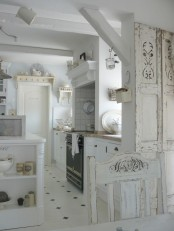 a vintage and shabby chic kitchen with white farmhouse furniture, an art deco cooker with tiles around and a shabby chic dining set