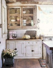 a rustic shabby chic kitchen with wooden cabinets, a dark stained kitchen island and stained floors and a large window
