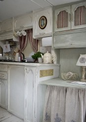 a neutral and pastel shabby chic kitchen with white cabinets, an olive green upper cabinet and a table, printed linens