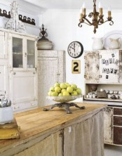 a shabby chic kitchen with neutral furniture, a kitchen island with burlap covering it, white cabinets, a vintage chandelier and some vintage decor