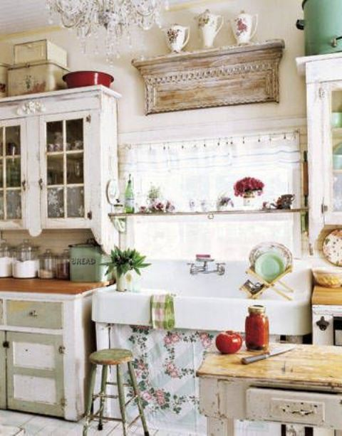 a bright shabby chic kitchen with olive green and white cabinets, a sink with a floral curtain, shabby chic wooden shelves, a crystal chandelier