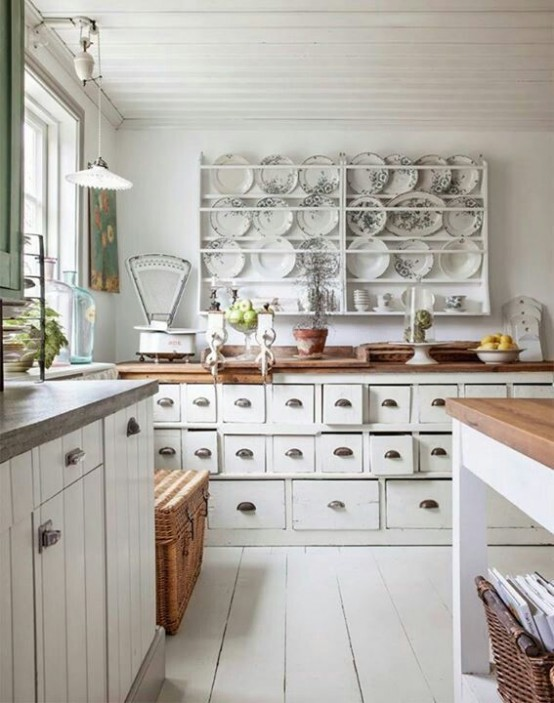 a white shabby chic kitchen with farmhouse cabinetry, a large display with floral plates, woven items and green touches