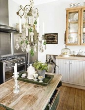 a charming farmhouse shabby chic kitchen with neutral cabinets, wooden glass ones, a crystal chandelier and a rustic kitchen island