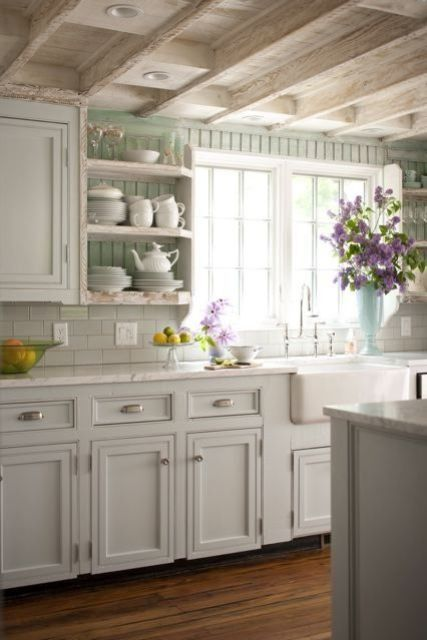 a charming white shabby chic kitchen with farmhouse cabinets, wooden beams on the ceiling, an aqua wall for a touch of color