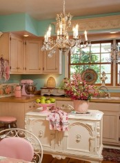 a delicate shabby chic kitchen with pastel green walls, white vintage furniture, a vintage chandelier, pastel pink touches and floral linens