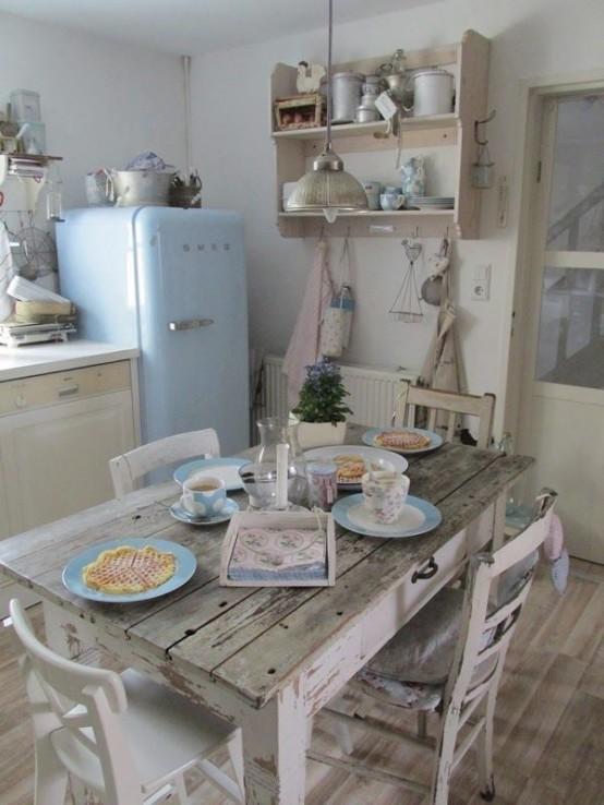 a neutral shabby chic kitchen with neutral and pastel furniture, a pastel blue fridge, a shabby chic table and chairs and printed linens