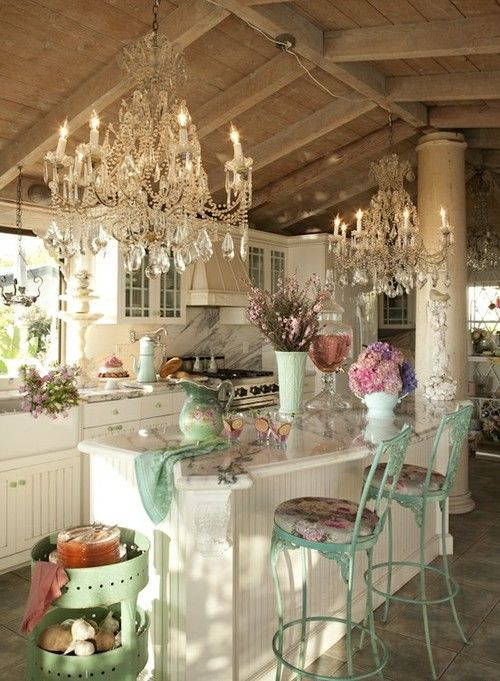 a vintage to shabby chic kitchen with white cabinets, a marble backsplash, crystal chandeliers and touches of mint and turquoise