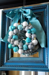 a pretty beach Christmas wreath of white, silver and turquoise ornaments, stars and a large ribbon bow on top is an amazing and chic idea