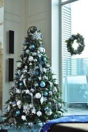a frozen Christmas tree decorated with blue and silver ornaments, ribbons, snowflakes and other plywood ornaments is a chic and cool idea