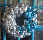 a pretty silver, white and blue Christmas wreath with feathers, beads and branches is a lovely decoration to rock