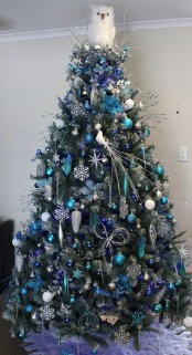 a lovely Christmas tree decorated with white and blue ornaments, snowflakes, branches, twigs and small birds is a beautiful idea to rock