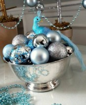 a silver bowl with silver and tiffany blue ornaments plus a tiny blue bird on top is a lovely Christmas centerpiece or decoration
