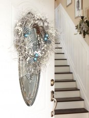 a frozen Christmas wreath with pinecones, ornaments and feathers, a ribbon bow and beads is a lovely decoration