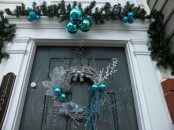 a silver and teal Christmas wreath with twigs, branches and ornaments and blue ornaments over the door for a truly winter feel