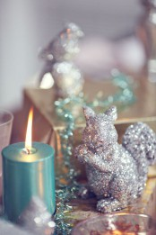 a silver glitter squirrel and a blue candle are a lovely and cool combo for cozy and glam Christmas decor
