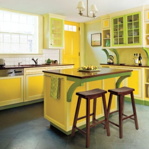 a stylish vintage kitchen with yellow and green cabinets, a neutral tile backsplash, a green wall and a bright yellow door