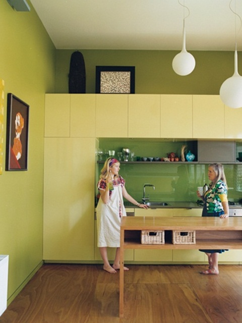 pistachio green walls, light yellow sleek cabinets and a bright green tile backsplash plus pendant lamps