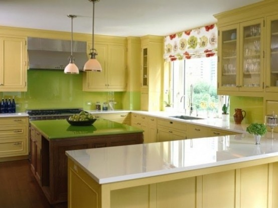 a vintage yellow kitchen with a green tile backsplash and a green tabletop on the kitchen island plus a floral curtain