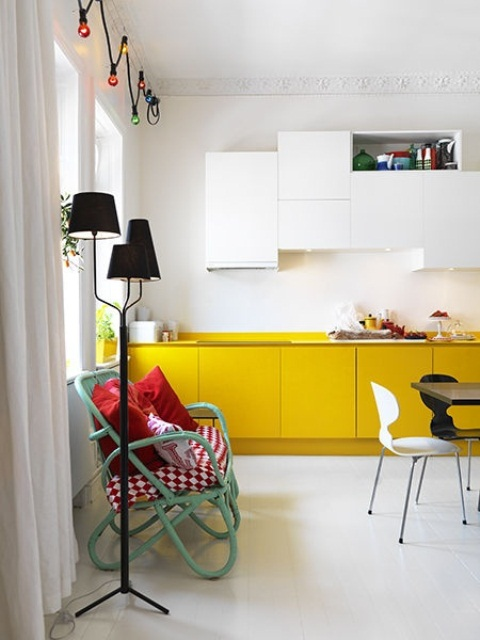 an eclectic kitchen with mustard lower cabinets and white uppers, with an aqua green bench and touches of black
