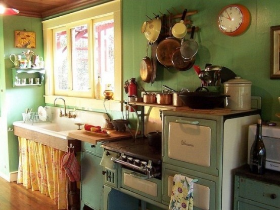 a vintage kitchen with green walls, cabinets and a bright yellow curtain under the sink