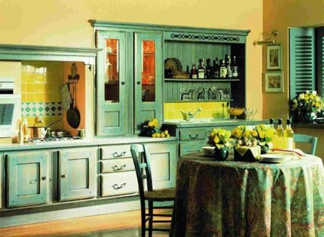 a vintage yellow kitchen with emerald cabinets, a yellow tile backsplash, a dining zone with green chairs and a green and yellow tablecloth