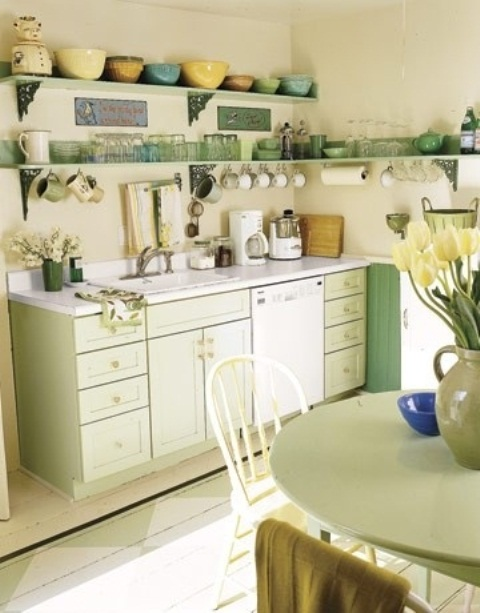 a bright vintage kitchen with light green cabinets, a green table, open shelves with green and yellow tableware