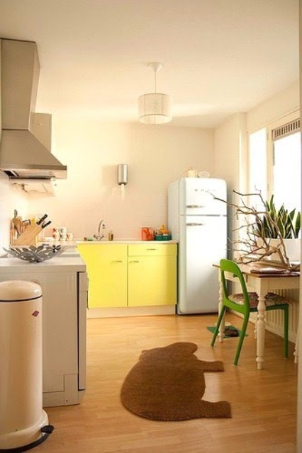 a neutral retro kitchen with a bright yellow cabinet, a mint fridge and a bold green chair and some succulents on the windowsill