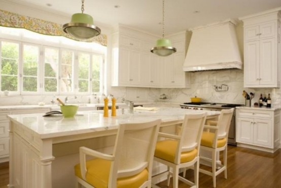 a refined white kitchen with a white marble backsplash and countertops, green pendant lamps and yellow chairs