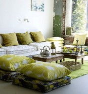 a summer living room in mustard shades, with lots of pillows and cushions and some fruits as additional decor