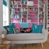 a bold hot pink wall, turquoise shades and matching colorful pillows make this living room feel like summer