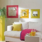 bold textiles, a sunny yellow plant stand and colorful frames enliven the living room making it feel summer-like