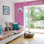 a hot pink wall, bright printed pillows and upholstery make the living room feel and look bright and summer-like