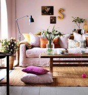 soft pastel and muted color textiles, blush walls and lots of blooms in pots and vases bring a summer feel to the room