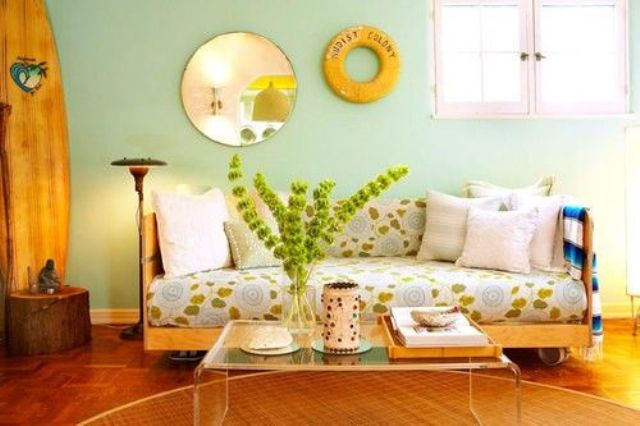 a colorful living room with mint walls, a botanical print sofa, an acrylic table, a mirror and some greenery in a vase