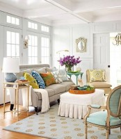 a welcoming neutral living room done with bright and colorful pillows, with a printed rug and some blooms in a vase
